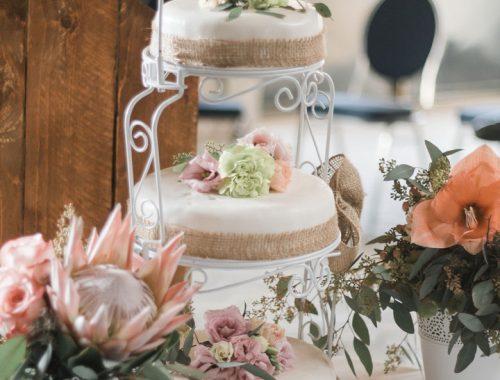 Die Vintagehochzeitstorte ist mit Hanfband verziert und mit blassgrünen Ranunkeln und apricotfarbenen Rosen dekoriert. Sie ist dreistöckig und steht auf einer schmiedeeisernen Etagere.