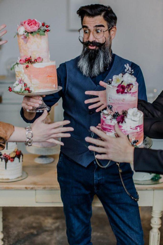Konditormeister Stefano Gallus hält zwei Torten, die andere Hände ihm wegschnappen möchten