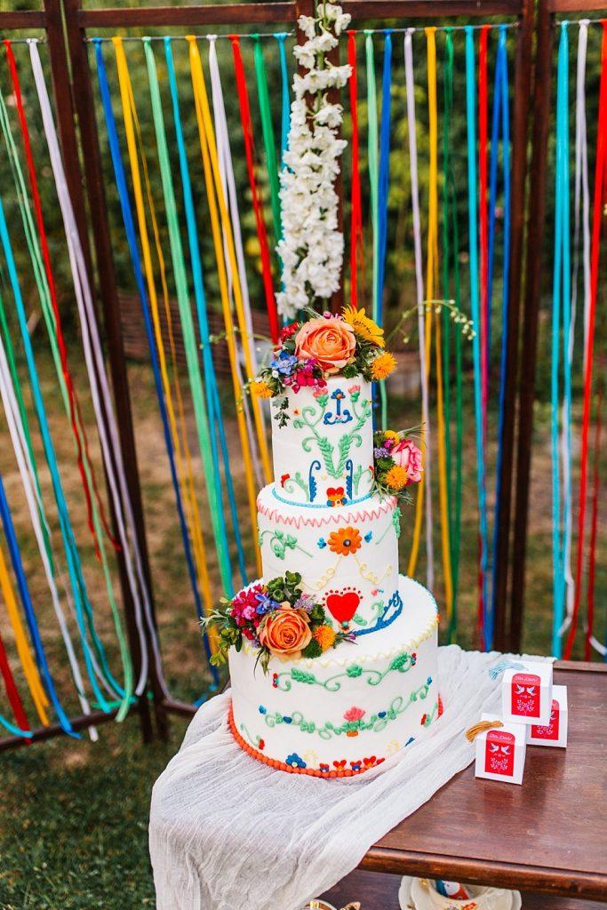 dreistöckige Hochzeitstorte mit Wiesenblumen und buntem Muster auf dem Fondant