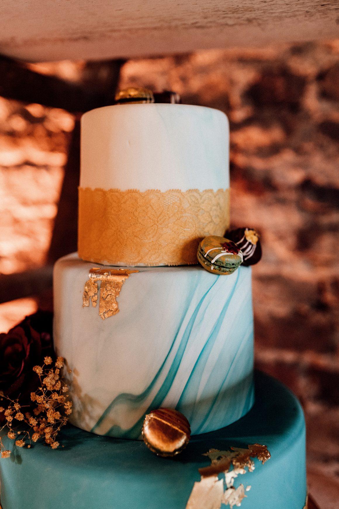 türkismarmorierte dreistöckige Hochzeitstorte mit goldenem Band und Macarons
