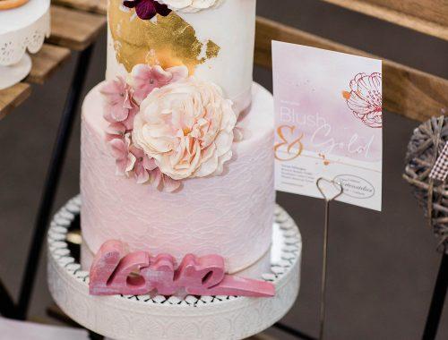Blushfarbene Hochzeitstorte mit Goldapplikationen und Ranunkeln